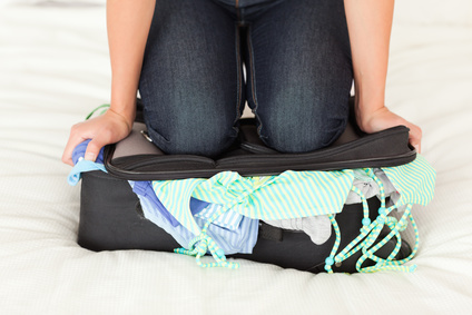 woman kneeinging on suitcase trying to close it
